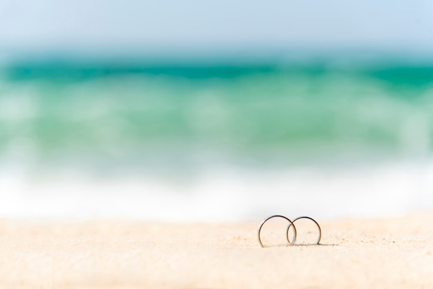 Couple engagement wedding rings on summer tropical sand beach with copy space. display design for honeymoon travel agency concept. wedding rings on sand with holiday vacation for couple propose marry