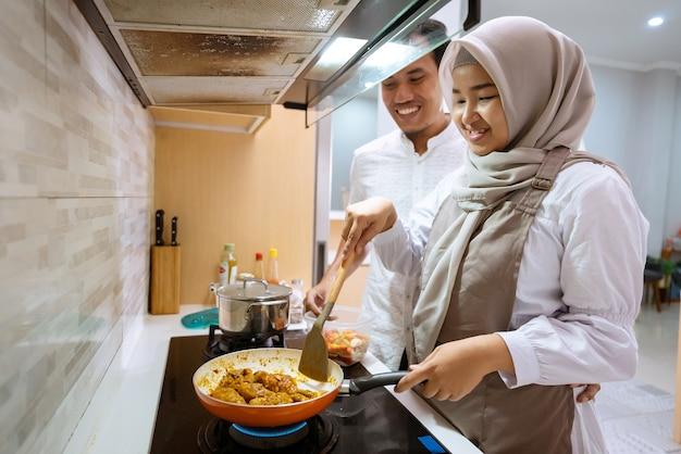 カップルは家で一緒に夕食を作るのを楽しんでいます。イフタールディナーの準備をしているイスラム教徒の女性と男性
