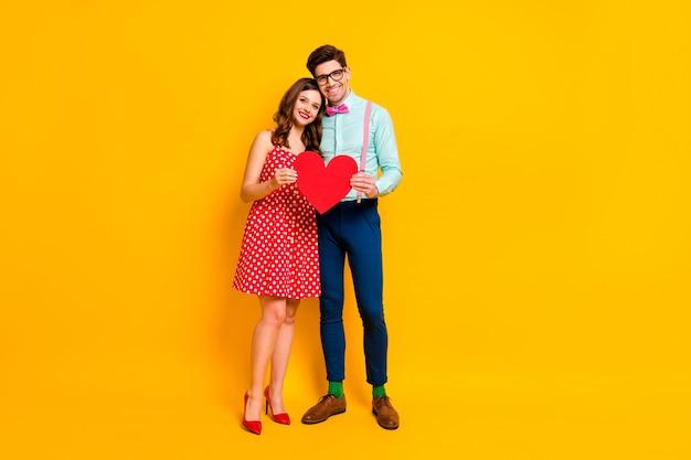 Пара наслаждается свиданием держать красную бумажную открытку сердце обнять