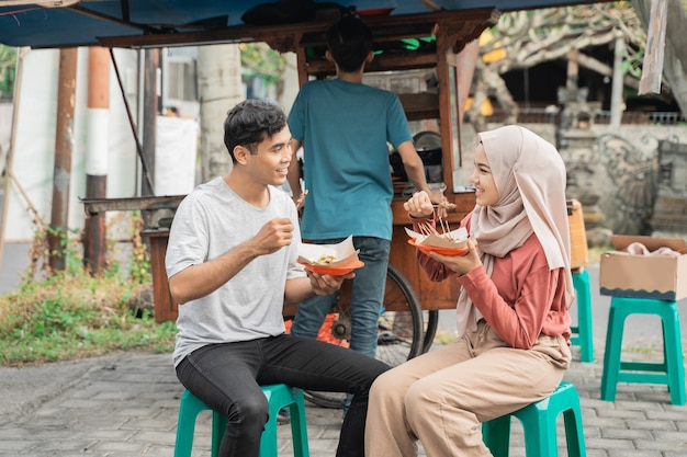 カップルはインドネシアの屋台の食べ物の売り手から購入したチキンサテを食べるのを楽しんでいます