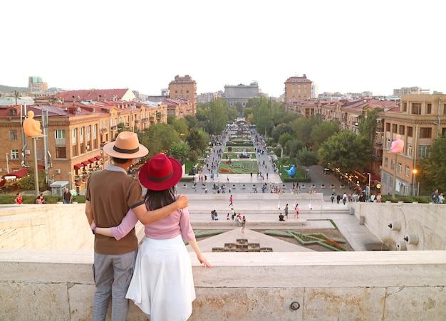 カップルは、アルメニアのエレバンカスケードからエレバンの印象的な夜の街の景色をお楽しみください