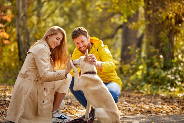 Couple enjoy time with dog in the autumn forest, happy man and woman are friends with nice dog