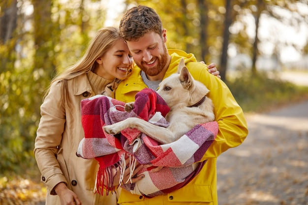 Couple enjoy the time with pet. lovely dog is wrapped in checkered red plaid, sitting on hands of male, at sunny autumn day in the forest countryside