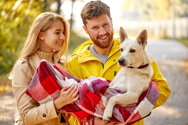 Couple enjoy walking with cute white dog in the nature, beautiful dog sits on hands of owners, man and woman smile