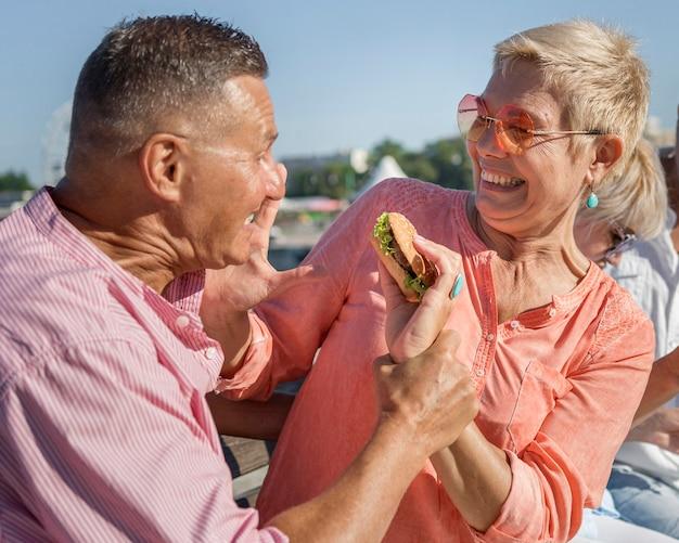 屋外でハンバーガーを楽しんでいるカップル