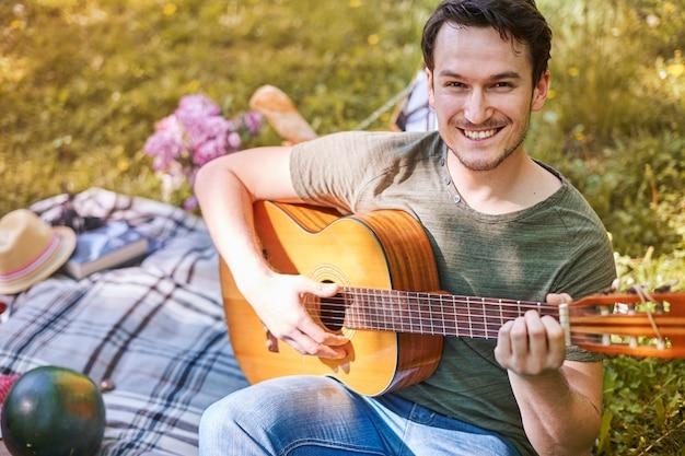 공원에서 피크닉을 즐기는 커플. 기타를 연주하는 남자. 로맨틱 데이트