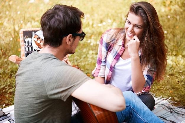 公園でピクニックを楽しんでいるカップル。ギターを弾く男。ロマンチックなデート