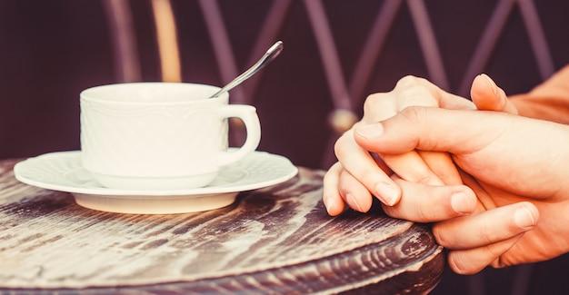 コーヒーを楽しむカップル。コーヒーのカップを保持している素敵なカップル