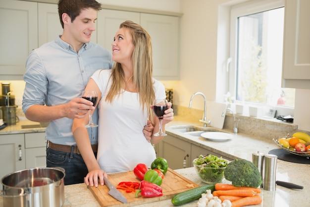 ワインを飲んで料理するカップル