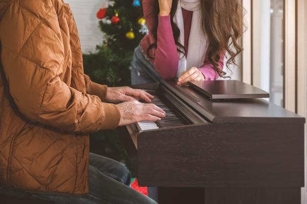 피아노와 함께 거실에서 좋은 시간을 즐기는 커플. 피아노를 연주하고 여자를 위해 노래하는 남자.