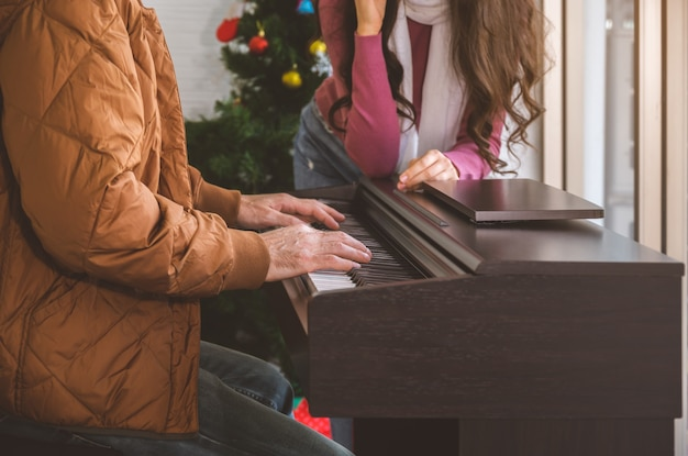Couple enjoying great time in living room with piano. man playing piano and singing for woman.