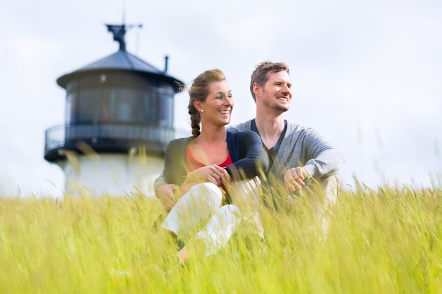 Couple enjoying holiday in front of lighthouse