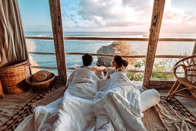 Uluwatu 발리, 인도네시아에서 편안한 휴가를보고 열대 해변 방갈로에서 아침 휴가를 즐기는 커플