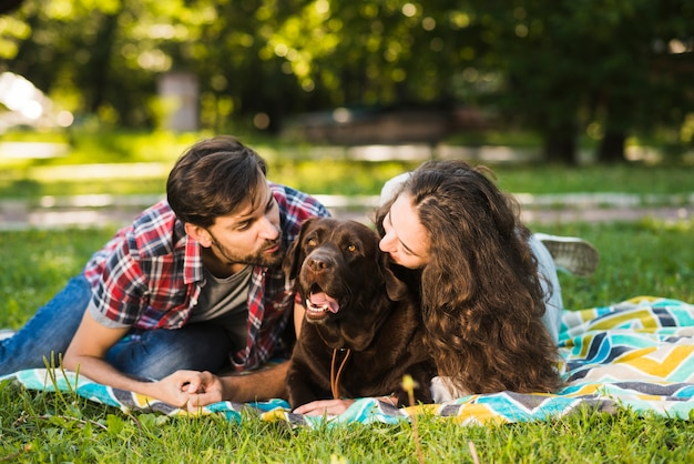 Couple enjoying picnic with their dog in park