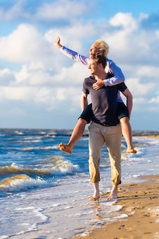 독일 북해 해변에서 낭만적 인 일몰을 즐기는 커플