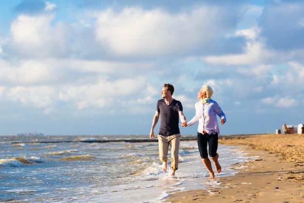 북 해 해변에서 낭만적 인 일몰을 즐기는 커플