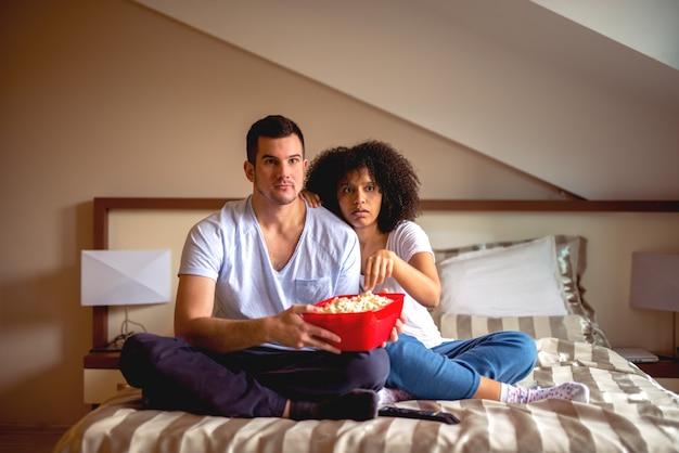 映画やポップコーンと自宅で時間を共有することを楽しんでいるカップル。