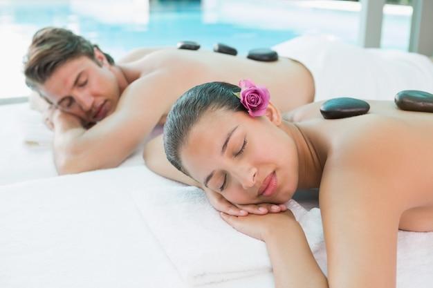 健康的なファームで石のマッサージを楽しむカップル