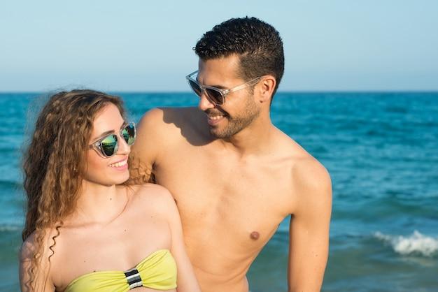 Пара, наслаждающаяся солнцем и солнечным днем у моря