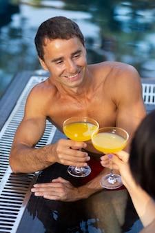 Пара, наслаждаясь своим днем в бассейне с напитками