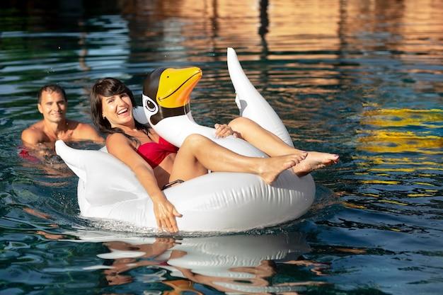 Пара, наслаждаясь своим днем в бассейне Бесплатные Фотографии