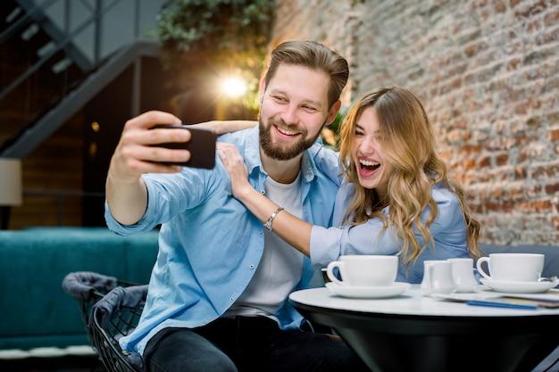 カップルが一緒に時間を楽しんで、selfieを作り、カフェのテーブルに座って、コーヒーを飲みます。