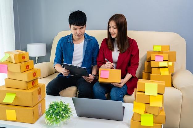 Пара предпринимателей работает и готовит посылку для доставки клиенту в домашнем офисе