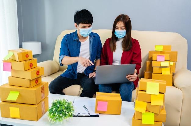Пара предпринимателей, работающих с ноутбуком, чтобы подготовить коробку для посылки для доставки покупателю в домашнем офисе, люди в маске для защиты от пандемии коронавируса