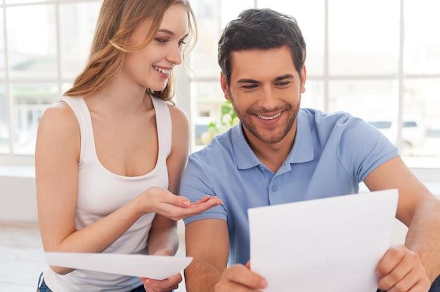 Пара изучает документы. веселая молодая пара изучает документы, сидя рядом друг с другом в своей квартире