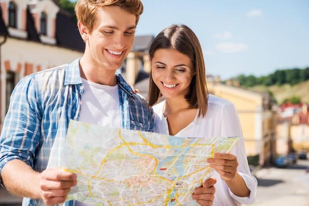 地図を調べるカップル。屋外に立っている間一緒に地図を調べる幸せな若い観光客のカップル