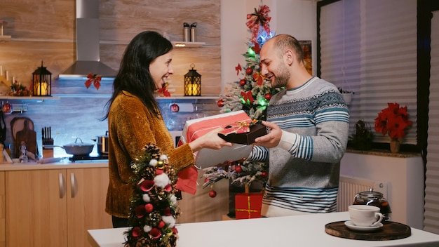 Couple exchanging presents for christmas eve festivity