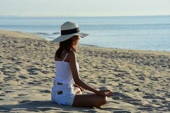 カップルエクササイズビーチでヨガをして、早朝の日の出でビーチでジャンプします。