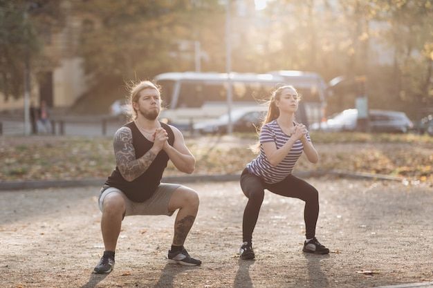 Couple exercise in park. training for perfect hips