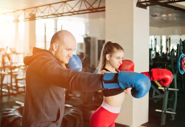 パンチを行使するカップル。若い女性と男性がジムでボクシンググローブのパンチをトレーニングしています。
