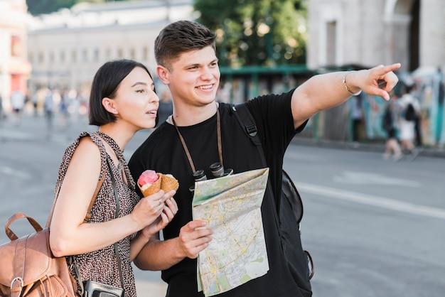 Пара, изучающая город с картой и мороженым