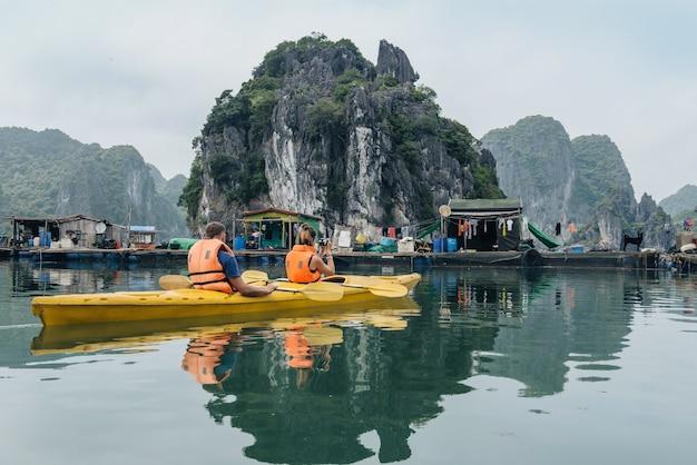 카약을 타고 떠 있는 마을을 탐험하고 보트에서 사진을 찍는 커플. 베트남 하롱베이 깟바섬