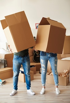 Couple faces behind cardboard boxes