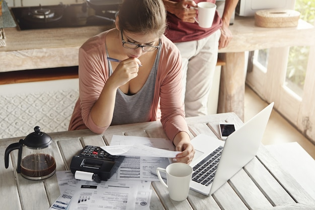Пара сталкивается с долговыми проблемами, не в состоянии выплатить ипотечный кредит. задумчивая женщина выглядит разочарованной, держит ручку, управляя семейным бюджетом, делая расчеты с помощью калькулятора и ноутбука