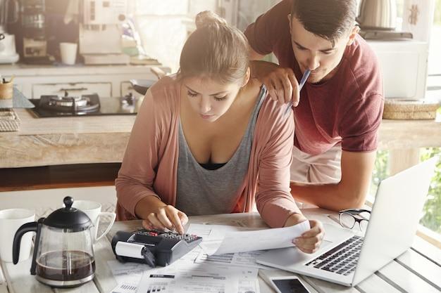 財政的ストレスに直面しているカップル。若い女性は、電卓を使用して台所でさりげなく家族の予算を計画して服を着せた。ペンを持って隣に立っている夫