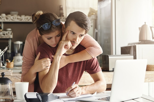 Couple facing financial stress. young thoughtful bearded man holding index finger on his temple planning family budget at home, using laptop and calculator. his supportive wife hugging him from behind