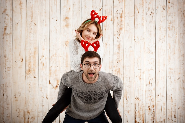 Couple in fake deer horns posing have fun over wooden wall