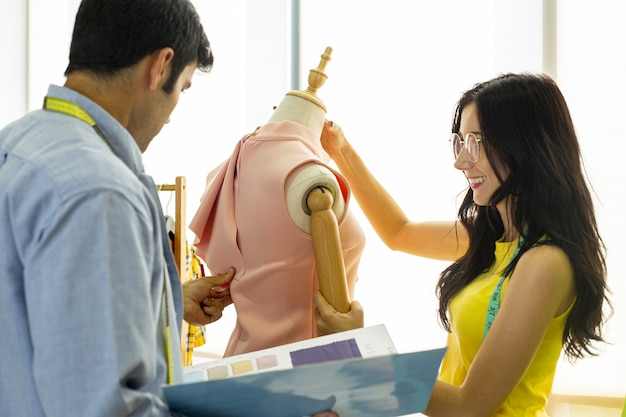 Couple fashion  designers are discussing and designing  their stylish cloth for new clothes collection
