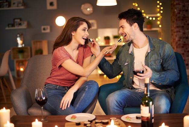 Пара кормит друг друга за ужином Premium Фотографии