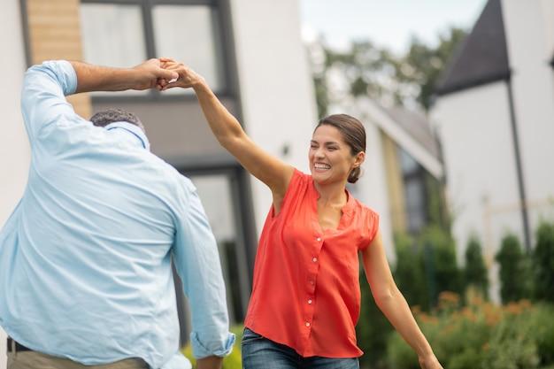 素晴らしい気分のカップル。家の近くで踊りながら素晴らしい気分の陽気な晴れやかなカップル