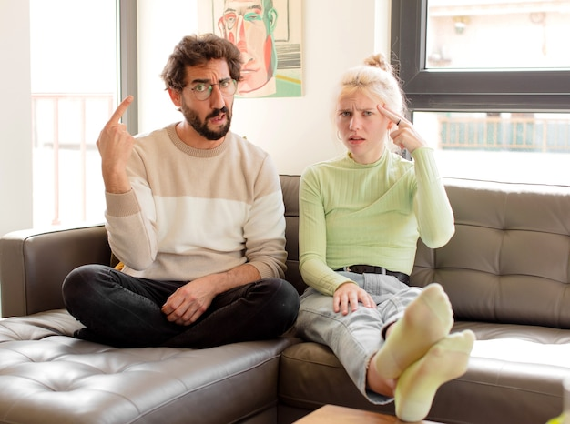 Couple  feeling confused and puzzled, showing you are insane, crazy or out of your mind
