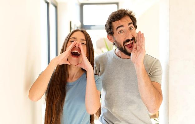 カップルは幸せ、興奮、前向きに感じ、口の横に手を置いて大きな叫び声を上げ、声をかけます