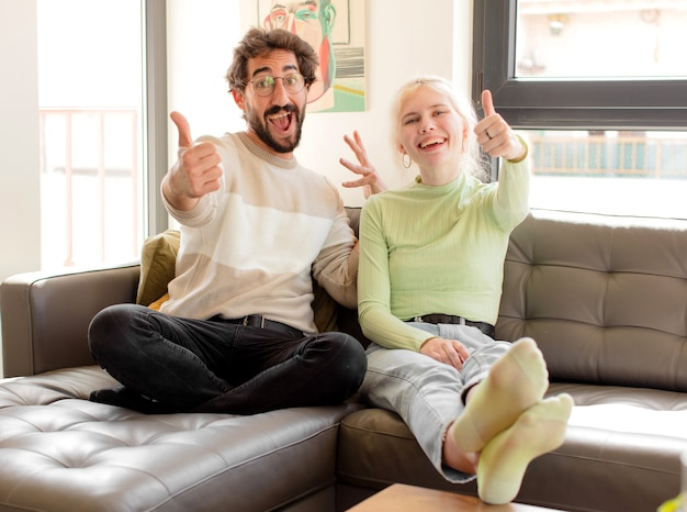 Couple  feeling proud, carefree, confident and happy, woman smiling positively with thumbs up