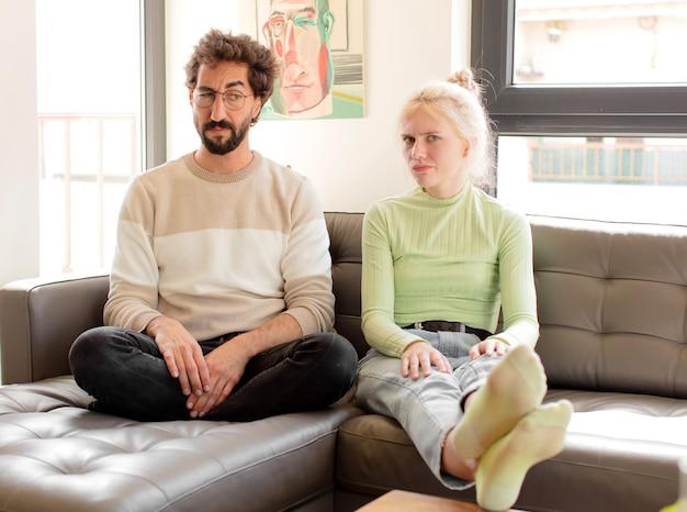 悲しみ、動揺、または怒りを感じ、否定的な態度で横を向いているカップルは、意見の相違に眉をひそめています