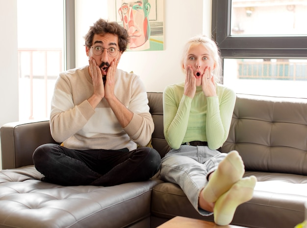 Couple feeling shocked and scared, looking terrified with open mouth and hands on cheeks