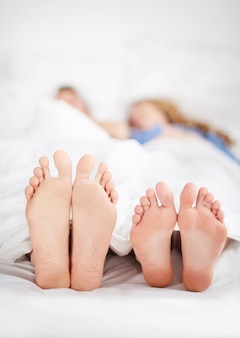 Couple feet sticking out of bed covers